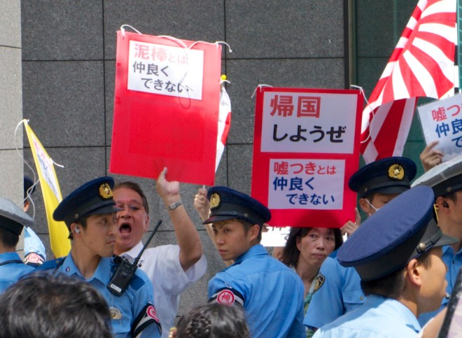 Anti-foreigner protesters in Osaka hold signs calling for foreigners to leave the country.